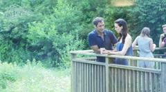 4K Attractive couple chatting and drinking coffee in natural outdoor area Stock Footage