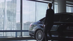 Driver opens the door for a businessman who speaks on the phone Stock Footage