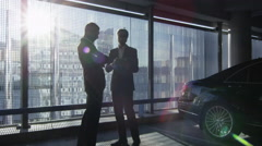 Two businessman have a conversation and reach an agreement with a handshake - stock footage