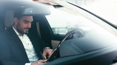 Businessman using tablet while sitting inside an executive black car Stock Footage