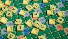 Scrabble Alphabet tiles falling on Scrabble Board Stock Footage