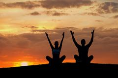 Boy and girl engage in yoga on the nature. - stock photo