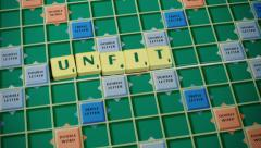 Hand spelling the word 'Unfit' with Scrabble Tiles - stock footage