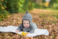 Beautiful baby crawling in fallen leaves - stock photo