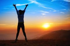 Silhouette of happy jumping young woman - stock photo