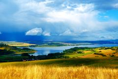 color landscape with storm clouds, green and yellow meadow and lake with village - stock photo