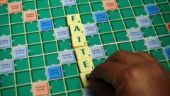 Hand spelling the word Fatter with Scrabble Tiles on Scrabble Board. 4k Video - stock footage
