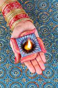 Stock Photo of Diwali Celebration Diya on a Female Hand