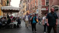 Tourists walk among the tables outside of the typical Roman trattorias Stock Footage