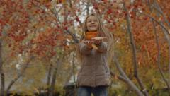 Stock Video Footage of Beautiful young girl surprised and pleased leaf falling