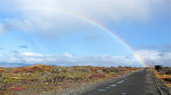 Rainbows end over country dirt road mossy lava field in autumn fall Iceland 4k - stock footage
