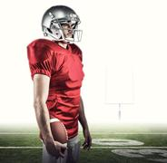 Composite image of serious american football player in red jersey looking away - stock photo