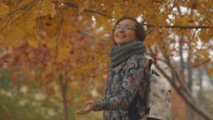 Young woman pleased fall of the leaves in autumn Stock Footage