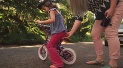 A mother helps her nervous daughter get started on her bicycle - stock footage