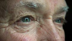 Old man opens his eyes: closeup portrait Stock Footage
