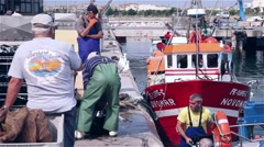 Boat being unloaded by fishermen in harbor Stock Footage