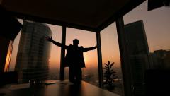 Businessman looking out the window in a contemplative way, Dolly shot, sunset Stock Footage