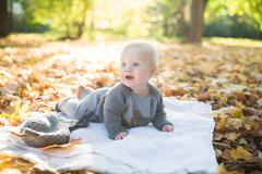 Beautiful baby crawling in fallen leaves Stock Photos