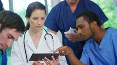 4K Experienced doctor in discussion with younger medical staff Stock Footage