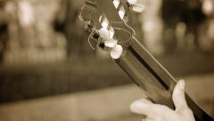 playing classical acoustic guitar in the street with people in background - stock footage