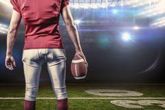 Composite image of mid section of american football player with ball - stock photo