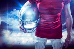 Composite image of american football player holding helmet aside Stock Photos