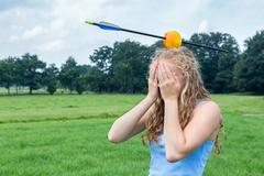 Teenage girl feeling fearful with apple and arrow on head - stock photo