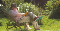 Elderly retired man relaxing outdoors reading a book enjoying retirement Stock Footage