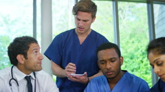4K Experienced doctor in discussion with younger medical staff - stock footage