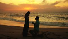 Young Man Proposing To Woman Sunset-Lit Beach Stock Footage