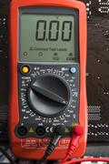 Red multimeter on motherboard background Stock Photos