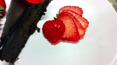 A dish of chocolate cake, strawberries and edible flowers, at a restaurant Stock Footage