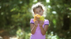 Teen nature girl portrait  holding yellow autumn leaves big green background Stock Footage
