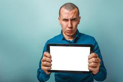 a man of European appearance thirty years shows a tablet frowns - stock photo