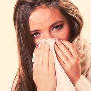 Sick woman girl with fever sneezing in tissue - stock photo