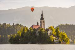 Catholic Church in Bled Lake, Slovenia with Hot Air Balloon Flying at Sunrise Stock Photos