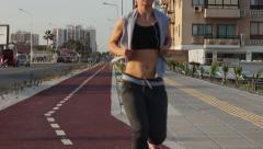 Stock Video Footage of Young independent woman doing morning run to be fit, active lifestyle in city