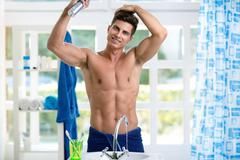 Young man making  hairstyle  in bathroom front mirror - stock photo