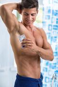 Stock Photo of Smiling man front mirror putting antiperspirant on armpit
