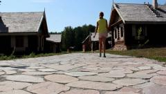 Girl goes on stone road in the village Stock Footage