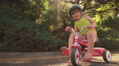 An adorable little girl sitting on her tricycle and smiling and then riding away Stock Footage