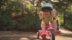 An adorable little girl sitting on her tricycle and smiling Stock Footage
