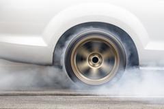 Race car burns rubber off its tires Stock Photos