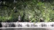 Stock Video Footage of Hikers is crossing the river