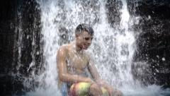 Male teenager under waterfall Stock Footage