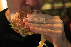 Man holding a hamburger - stock photo