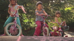 Three sisters sitting on their bikes and smiling Stock Footage