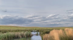 Time Lapse of Clouds Passing Over Wetlands and a Field Stock Footage