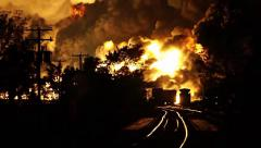 Large crude oil fed fire rising above train tracks at night Stock Footage