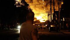 Man standing in front of large wall of fire at rail disaster - stock footage